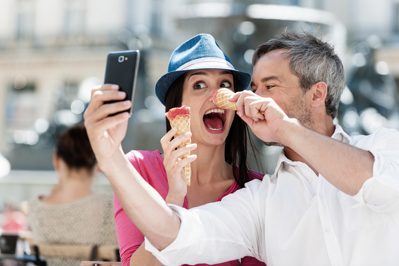 Portrait of a smiling couple eating ice cream and having fun in the city. The grey hair man with a beard in a white shirt is taking a picture with phone. The woman is wearing a blue hat and a pink top. They are making faces with their ice cream.